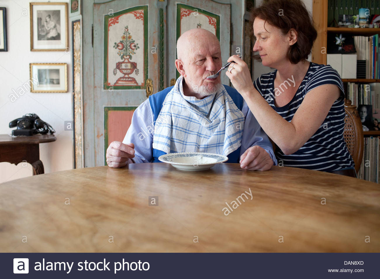Granddaughter feeding to her grandfather - Stock Image