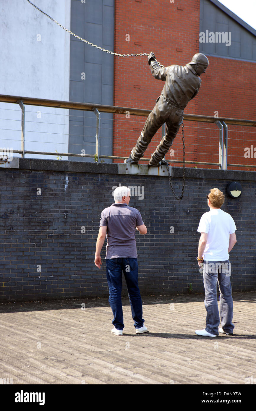 Men looking at the statue commemorating the shipbuilding history of the Clyde at Braehead in Glasgow. - Stock Image