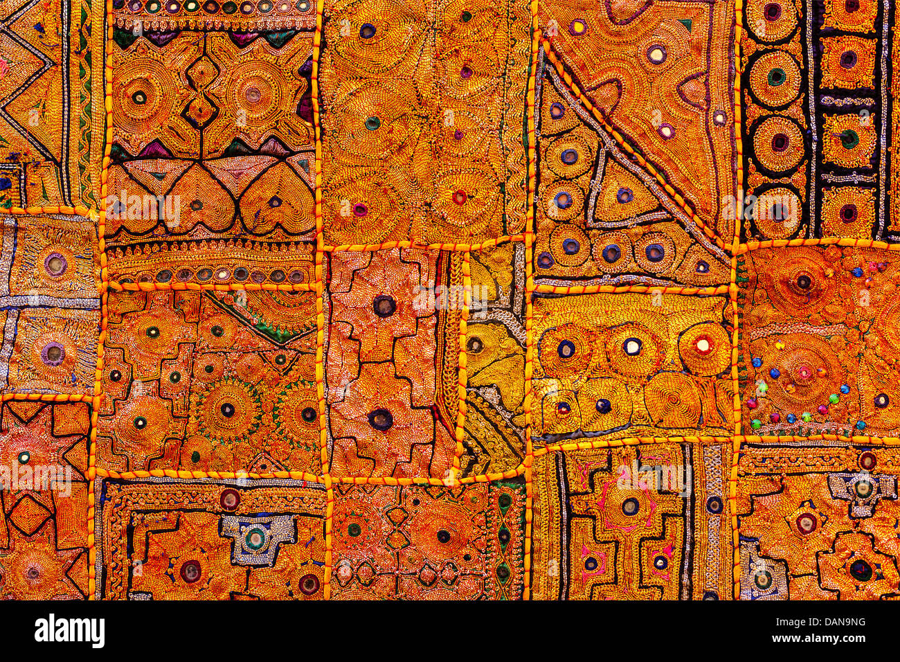 Colorful indian fabric textile texture background patchwork carpet quilt. India - Stock Image