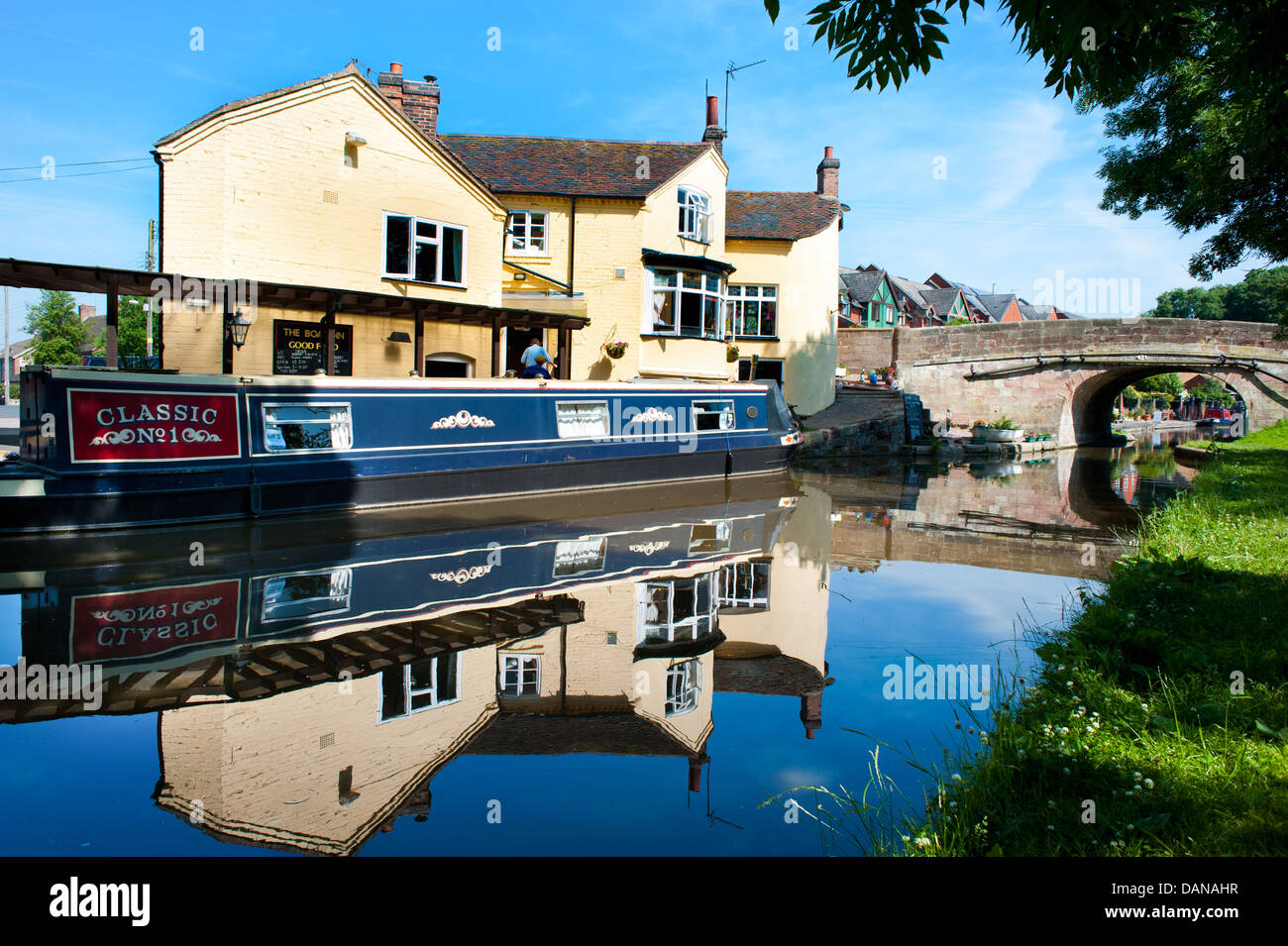 A canal boat on the Shropshire Union Canal by The Boat Inn pub, Gnosall Bridge, Staffordshire - Stock Image