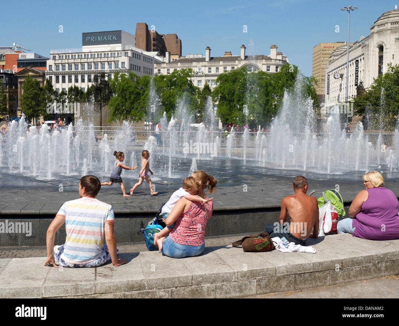 Manchester,UK,Tuesday 16th July. People enjoying the continuing hot sunny weather whilst cooling of in the fountain - Stock Image