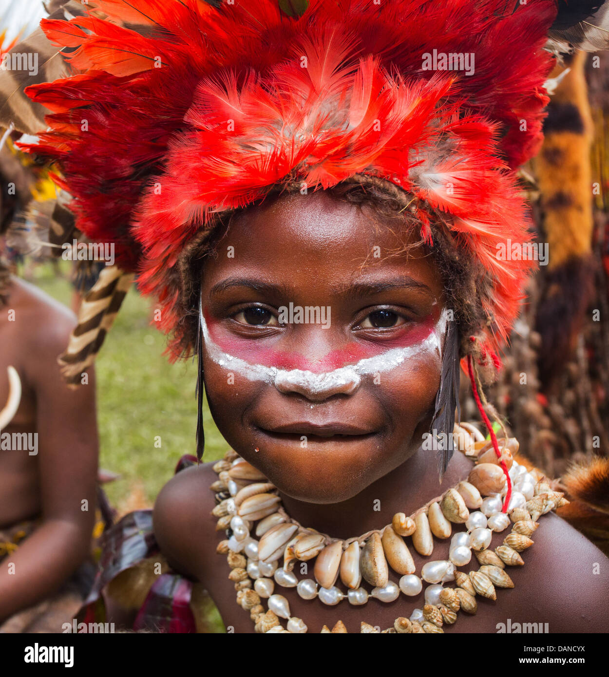 Young girl wearing a bright red feather headdress and necklace made of shells, Goroka show, Papua New Guinea - Stock Image