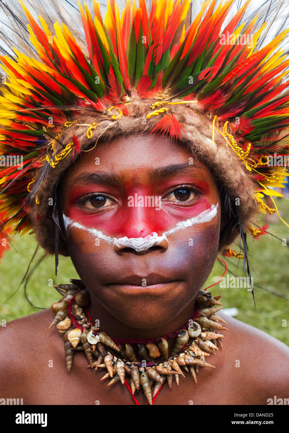Young boy wearing a brightly coloured headdress made from lorikeet feathers, Goroka show, Papua New Guinea - Stock Image