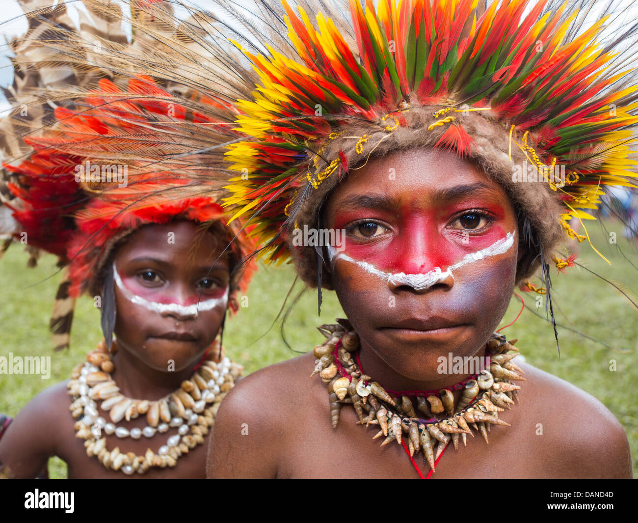 Children wearing a brightly coloured feather headdress made from lorikeet feathers, Goroka show, Papua New Guinea - Stock Image