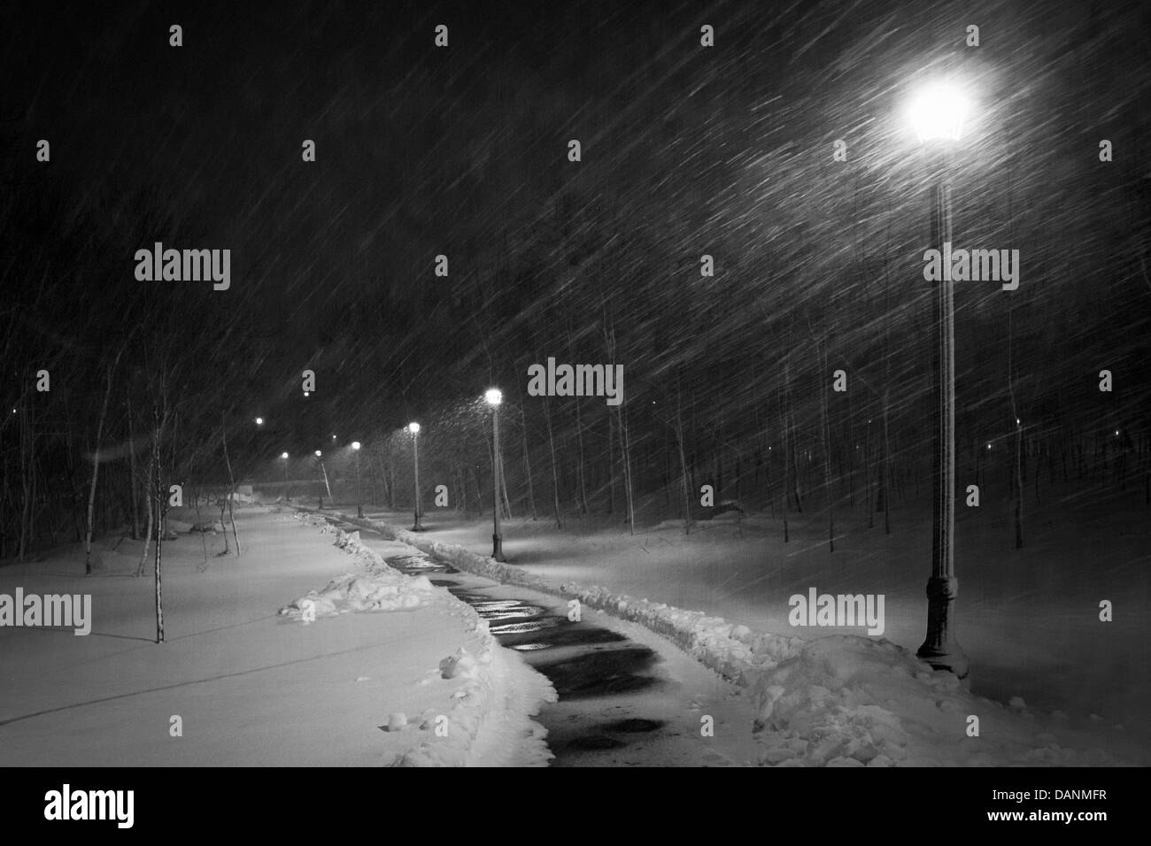 Snow blows across a lighted path at night. - Stock Image