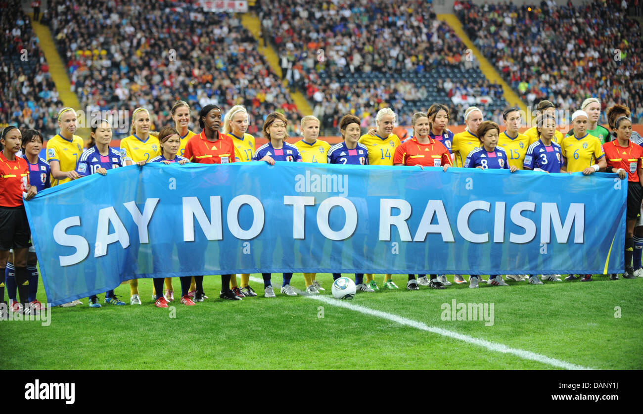 The teams of Japan, Sweden, and the referee team hold a banner reading 'Say No To Racism' prior the - Stock Image