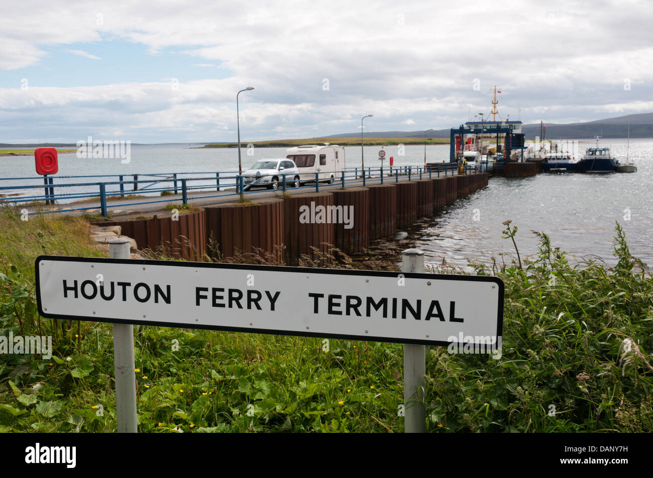 Sign for Houton Ferry Terminal on Orkney Mainland with vehicles leaving ferry in background. Stock Photo
