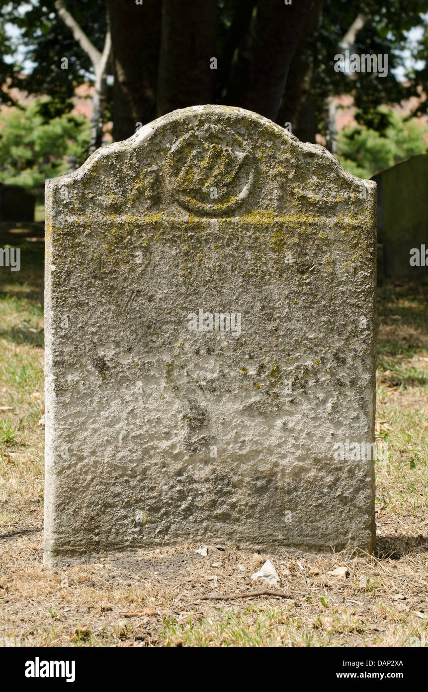 Old weathered gravestone in an ancient cemetery - Stock Image