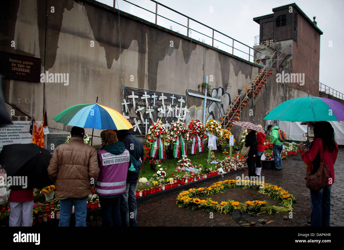 People stand at the scene of the accident at  the former premises of the Loveparade in Duisburg, Germany, 24 July - Stock Image