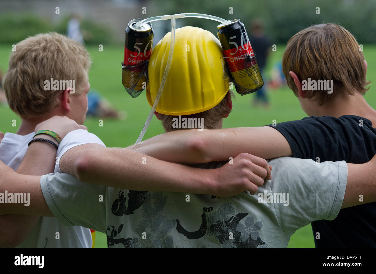 A young man with a beer can helmet is surrounded by his friends at the Neckarwiesen in Heidelberg, Germany, 27 July - Stock Image