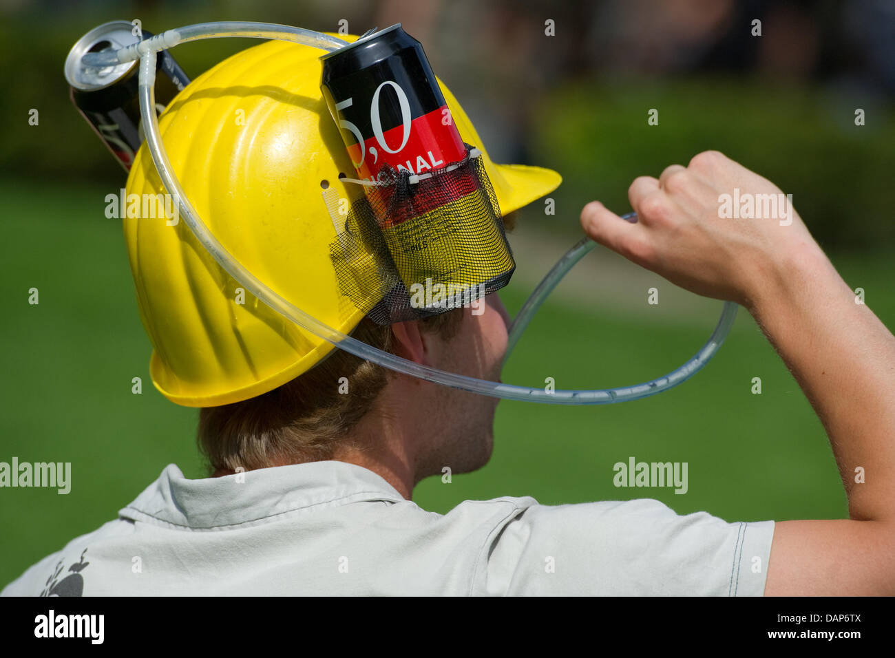 A young man with a beer can helmet drinks at the Neckarwiesen in Heidelberg, Germany, 27 July 2011. The police - Stock Image