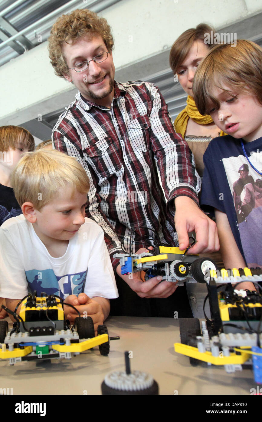 Accompanied by the student of computer science and engineering, Oliver Tretau (C), children check the funcionality - Stock Image