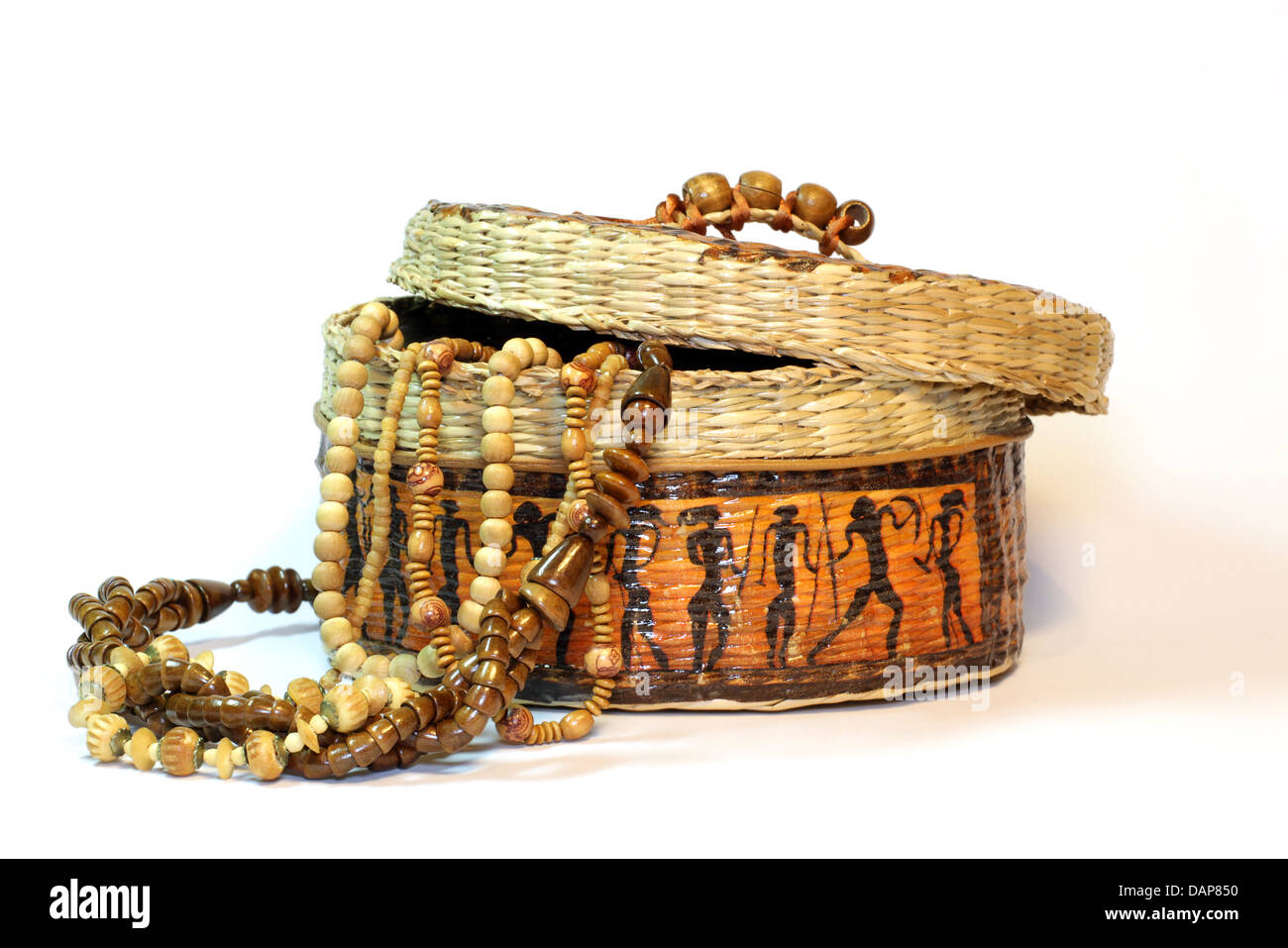 wooden and ivory beads in a handmade african box on a white background - Stock Image