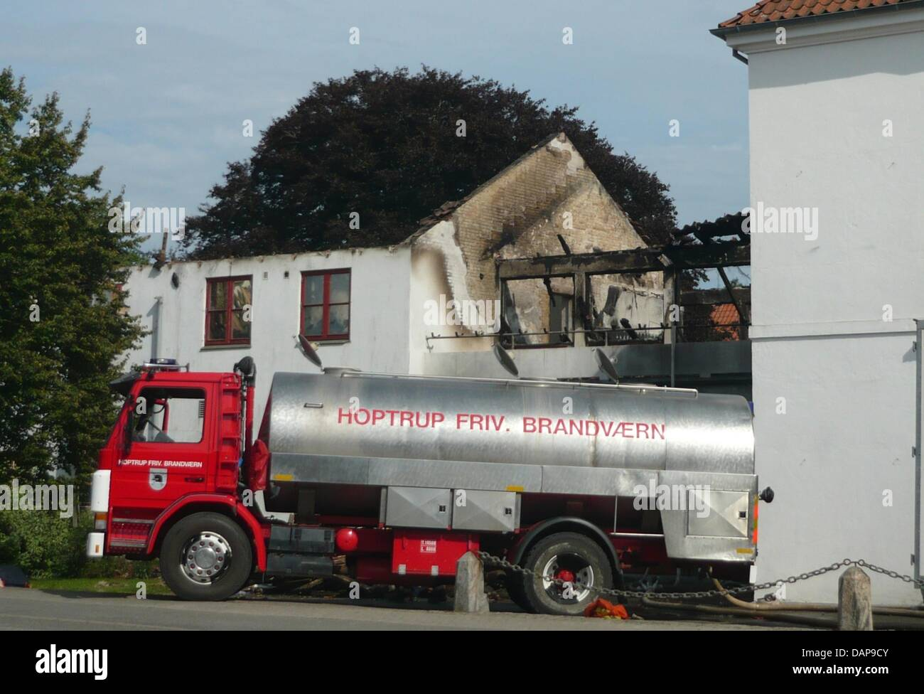 A vehicle of the volunteer fire department Hoptrup stands in front of a burnt out school hall of residence 'Hoptrup - Stock Image