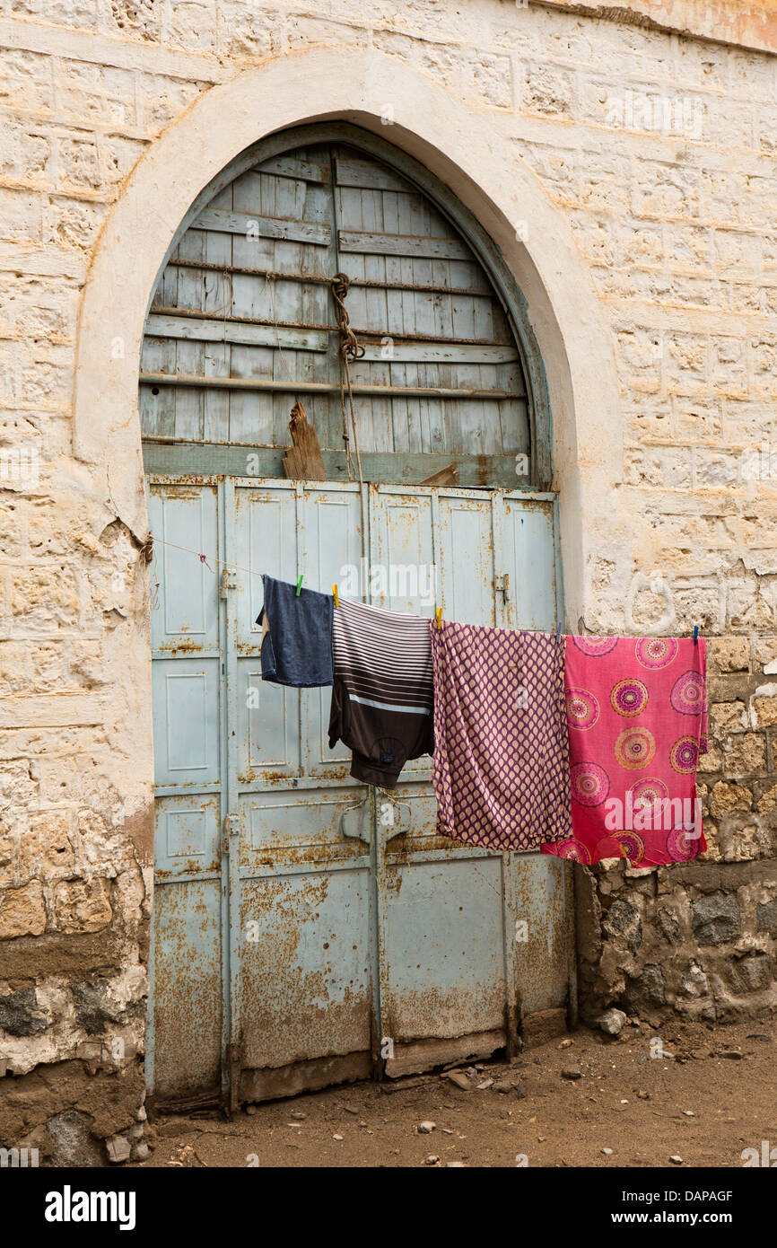 Africa, Eritrea, Massawa, Old Town, washing hanging on line outside blue painted Ottoman arched door Stock Photo
