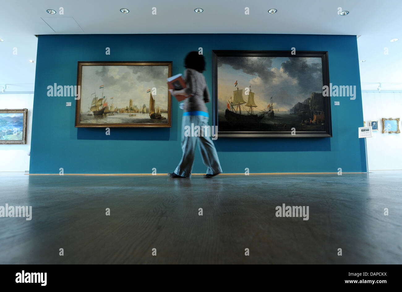A woman walks past two paintings at the Picture Gallery at the Willhelmshoehe Palace in Kassel, Germany, 11 August - Stock Image