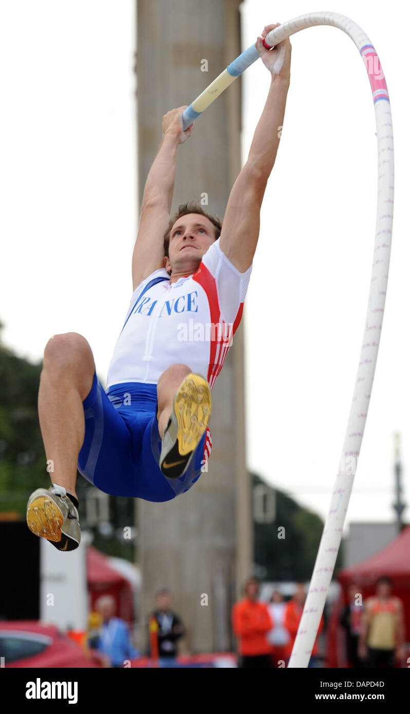 France's Renaud Lavillenie (European champion in the pole vault) jumps the bar in front of the Brandenburg Gate - Stock Image