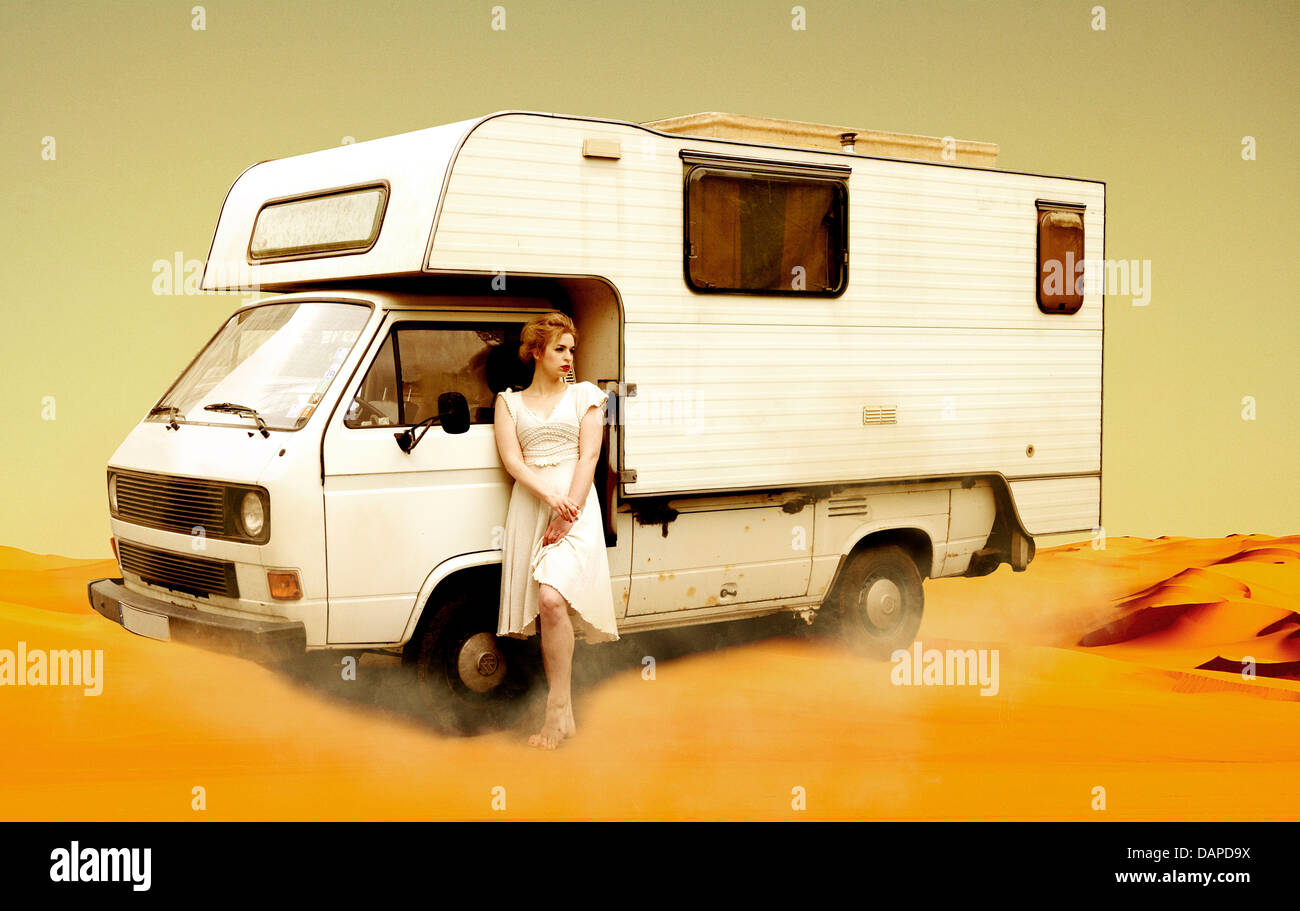 Germany, Berlin, Young woman standing next to camping bus in desert Stock Photo