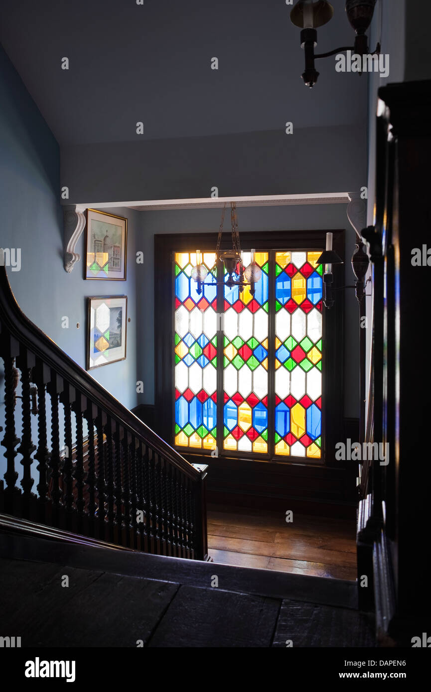 View Down Staircase With Wooden Balustrade To Landing With Stained Glass  Window
