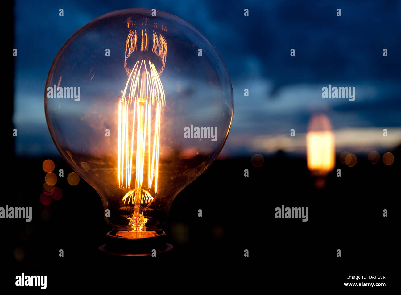 Close up of round bulb with nice filaments, sunset and reflections of light in background, landscape. - Stock Image