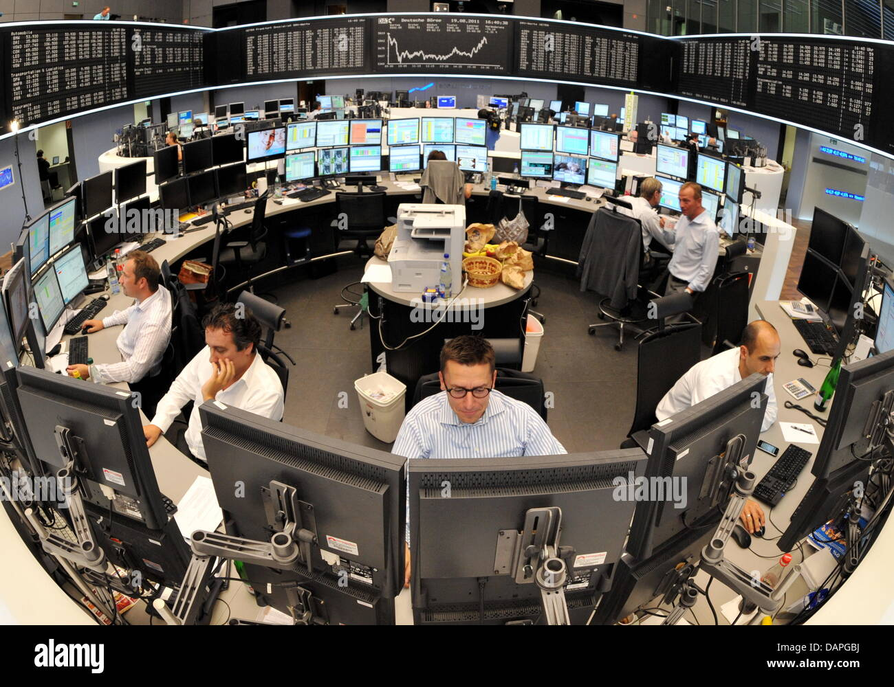 Employees look at their computer screens at the stock market in Frankfurt am Main, Germany, 19 August 2011. - Stock Image