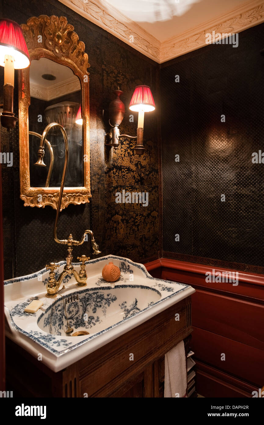 Antique blue and white porcelain basin and gilt mirror flanked by wall sconces with red lampshades - Stock Image