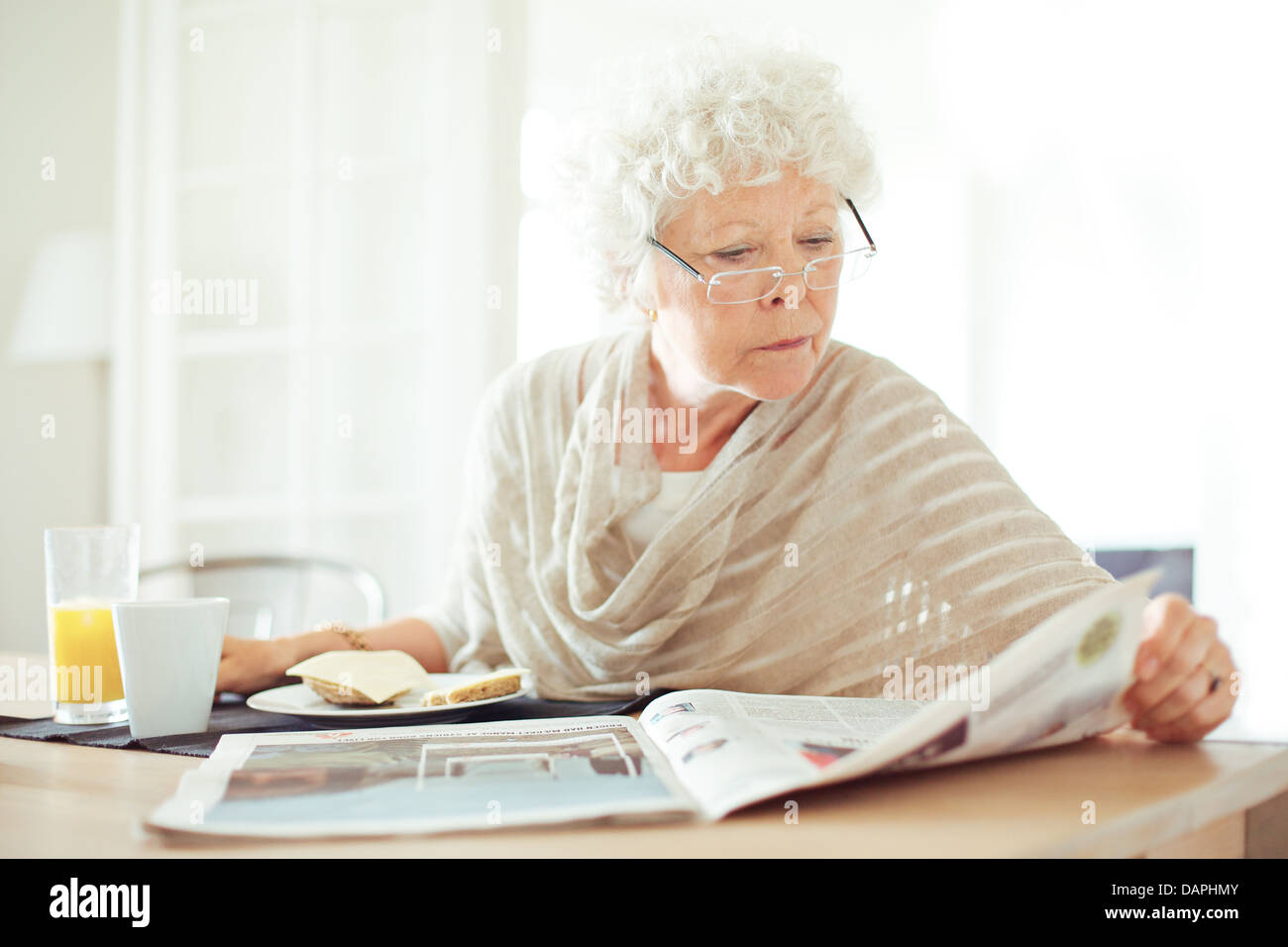 Relaxed senior woman having her breakfast and reading the morning news - Stock Image