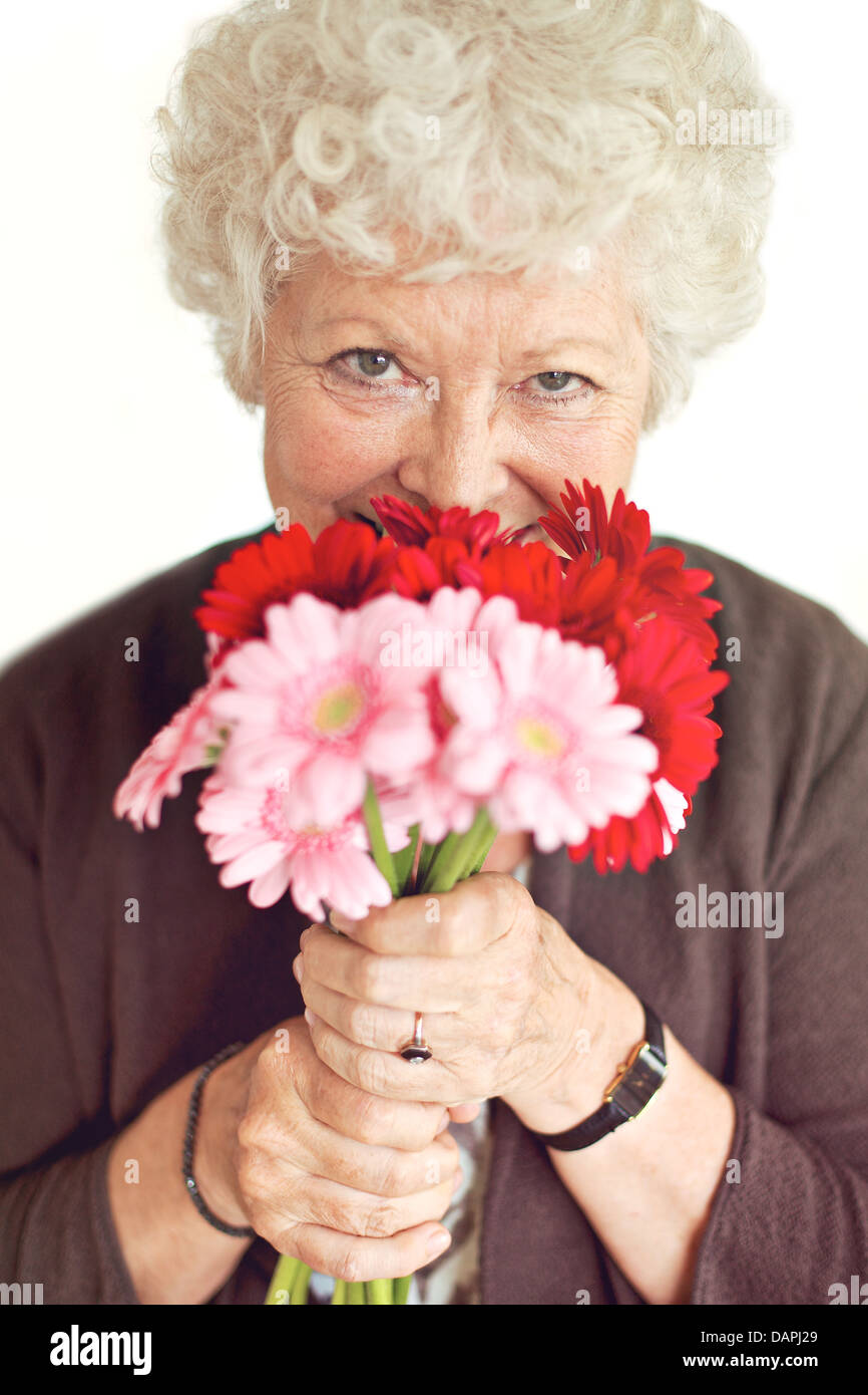 Cheerful grandmother happy to have received flowers on mother's day Stock Photo
