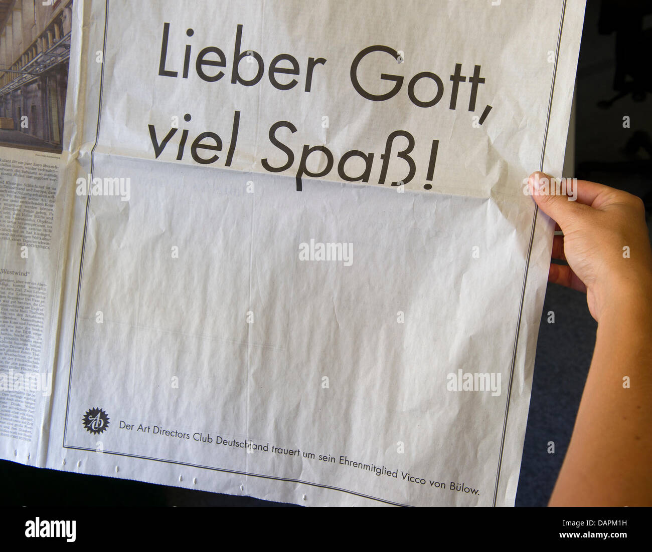 ILLUSTRATION - A full-page obituary of a supraregional newspaper for died comedian Viktor von Buelow alias Loriot, stating 'Dear God, have fun!', is hold by a woman in Munich, Germany, 26 August 2011. The death notice was commissioned by the Art Directors Club Germany, whose honory member Loriot had been. Loriot died at the age of 87 on 22 August 2011. Photo: PETER KNEFFEL Stock Photo
