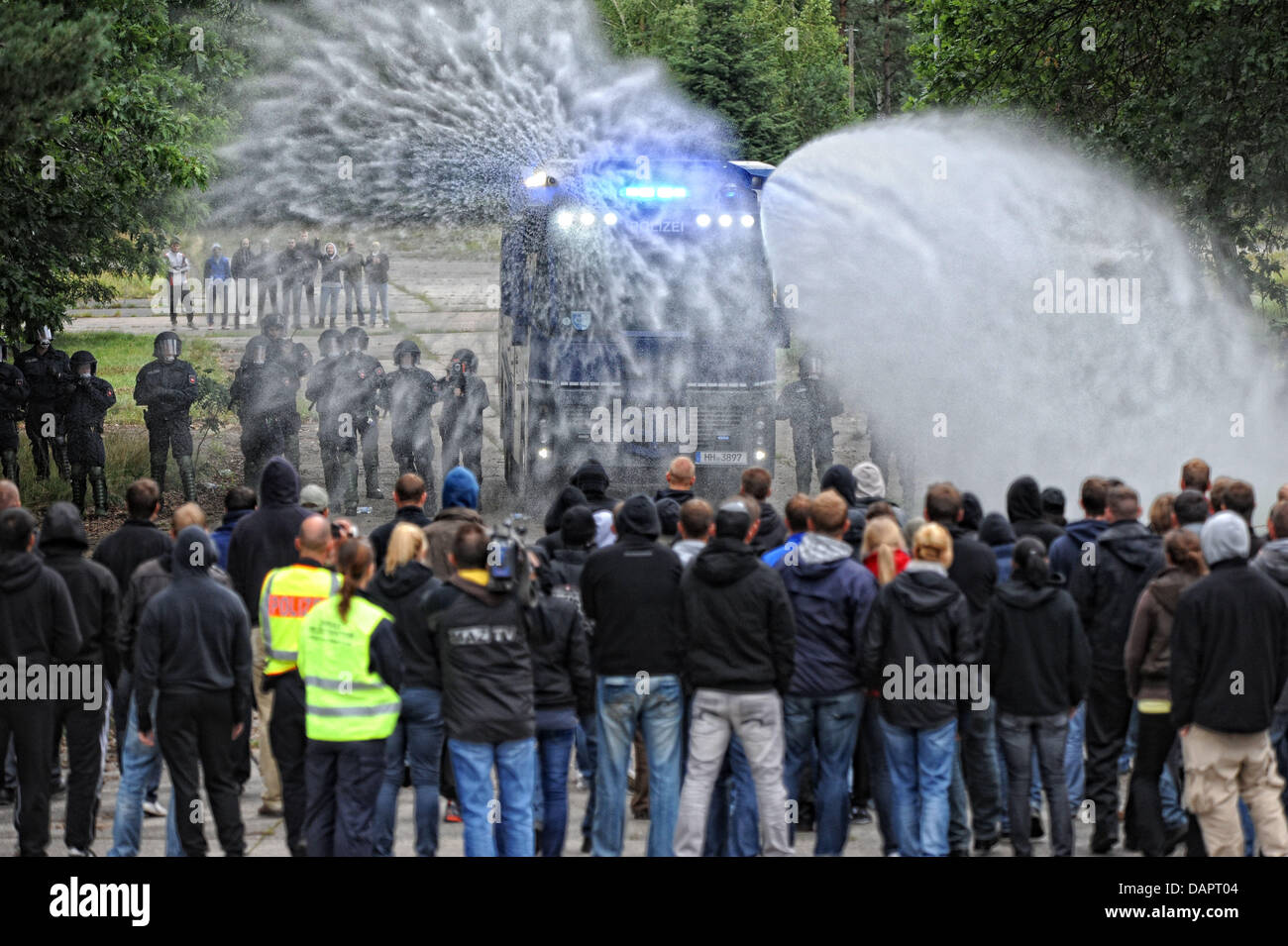 Police officers and demonstrators stand next to a water cannon vehicle during a drill inCelle,Germany, - Stock Image