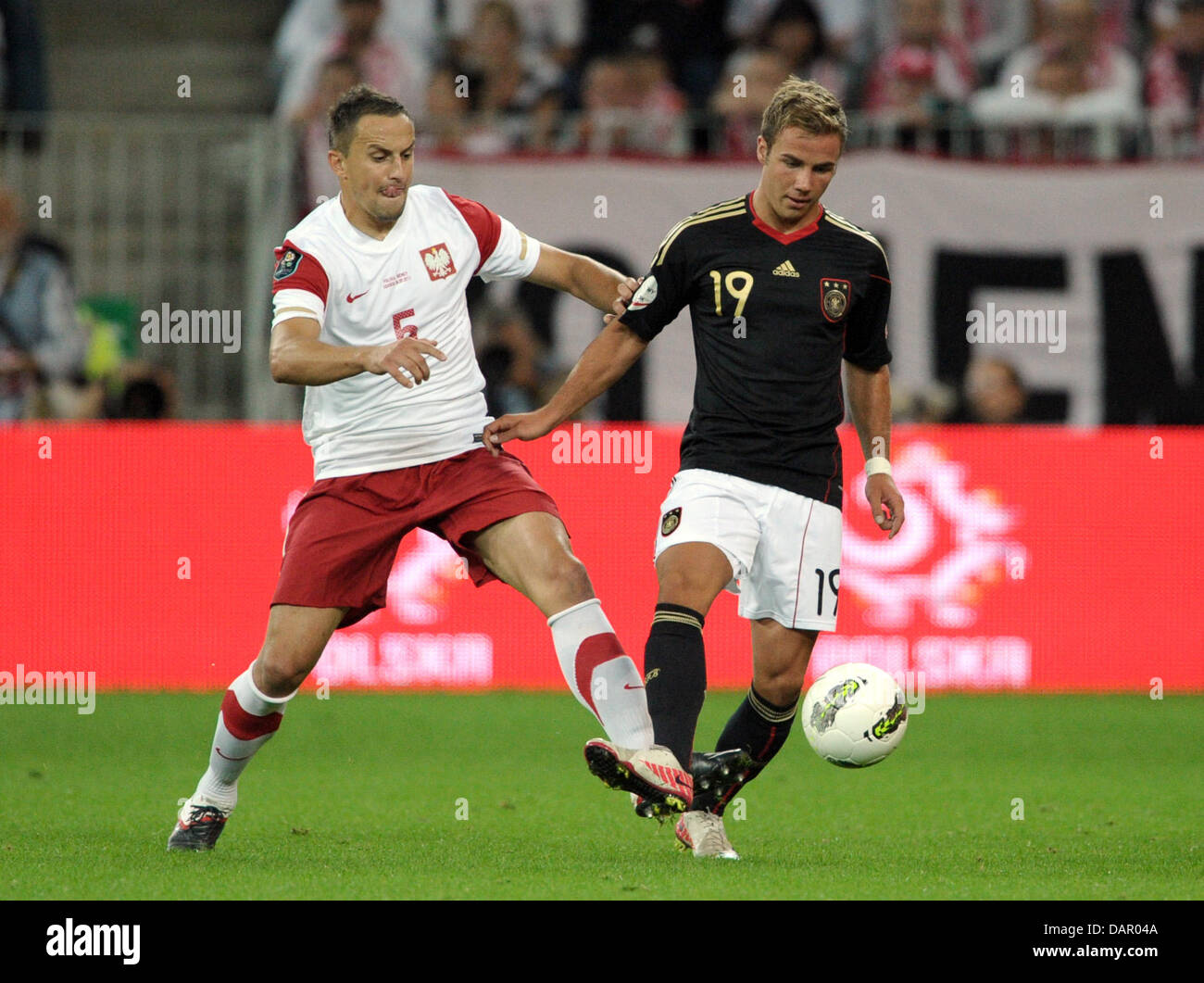 Poland's Dariusz Dudka (L) and Germany's Mario Götze fight for the