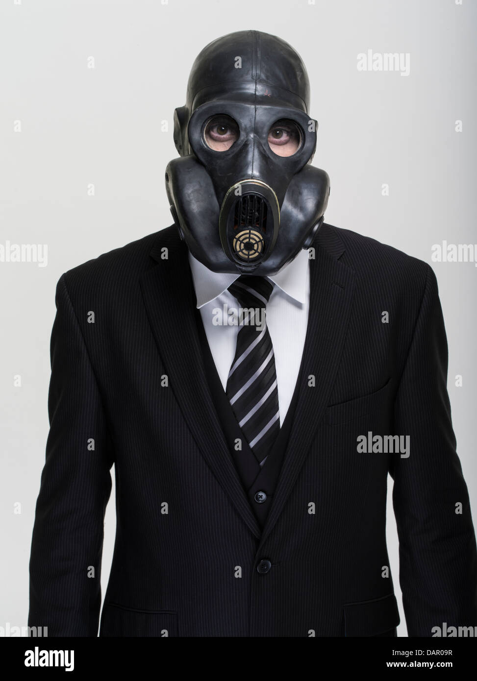 Businessman in suit and tie wearing gas mask. Toxic banking. - Stock Image