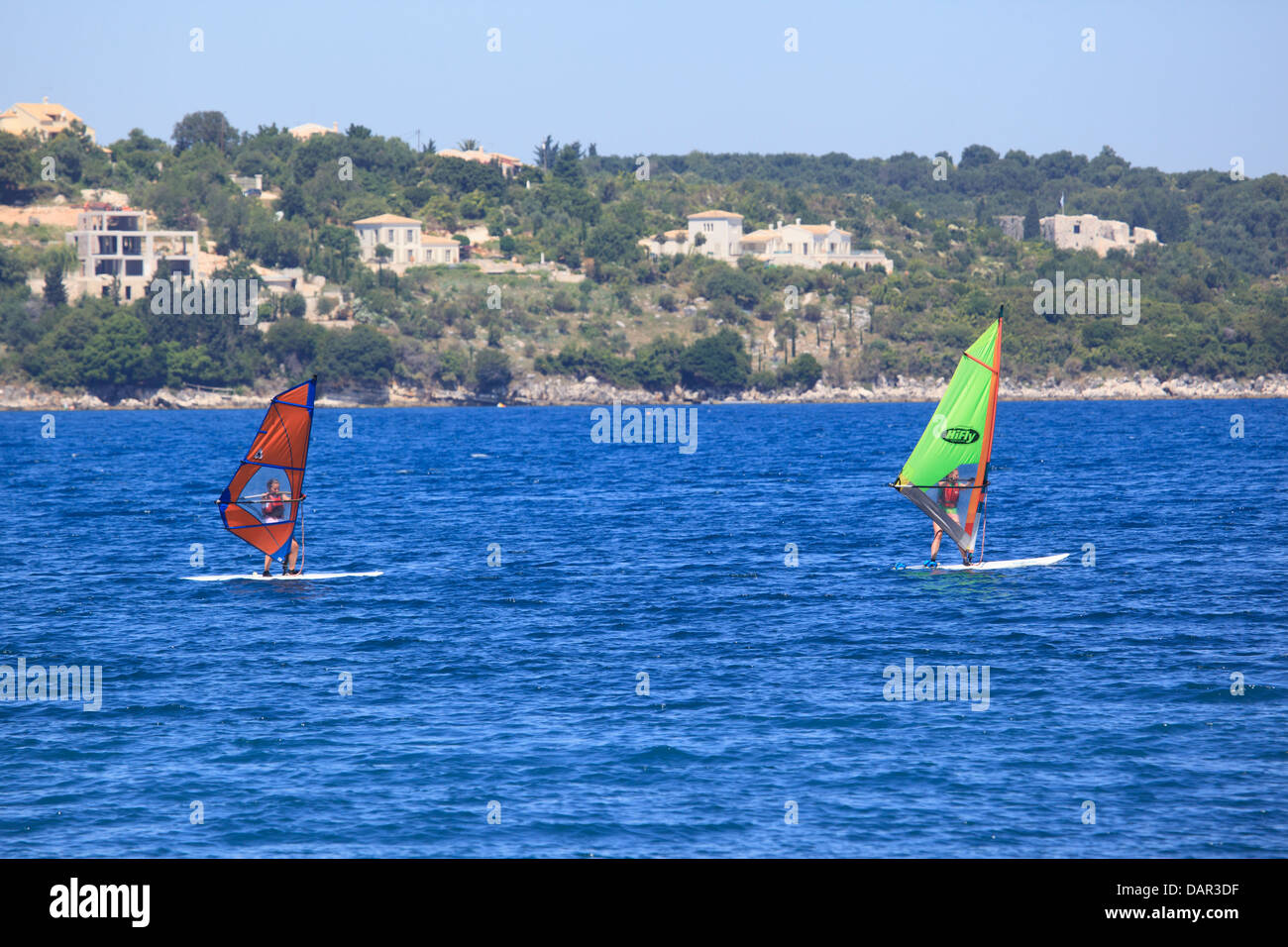 Two young women wind-surfing in Avlaki bay - Stock Image