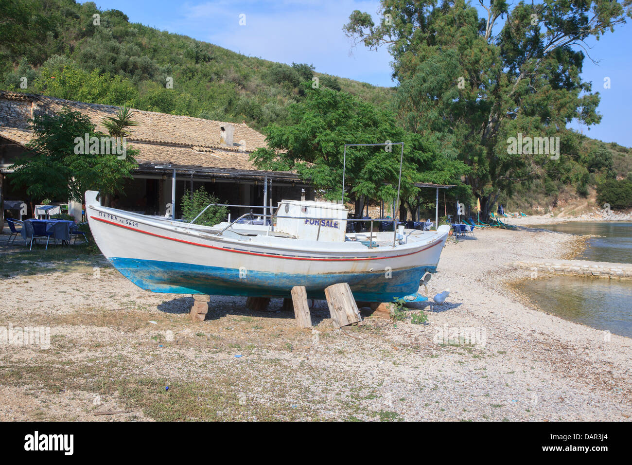 Old boat with For Sale sign in front of the Eucalyptus restaurant in Agios Stephanos Corfu - Stock Image
