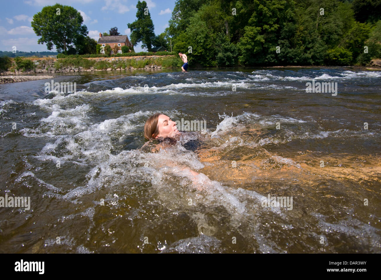 As temperatures reach 30ºC holidaymaker Julie Burrows from Norfolk cools off in the River Wye at Hay on Wye, - Stock Image