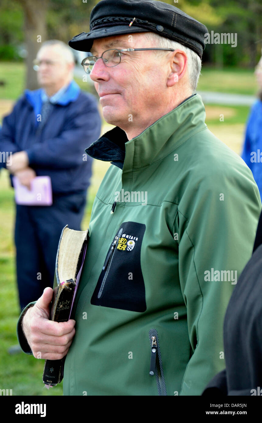 A man clutches his Bible and listens to a sermon at the Easter Sunrise Service in Greenbelt, Maryland - Stock Image