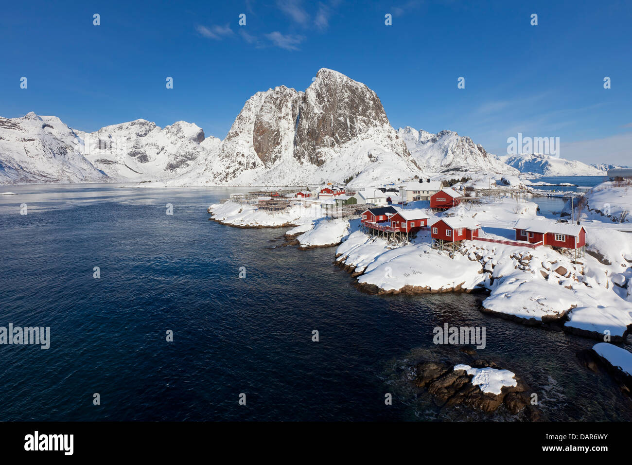 Rorbuer cabins and wooden racks with drying stockfish at Hamnøy / Hamnoy in the snow in winter, Lofoten, Nordland, Stock Photo