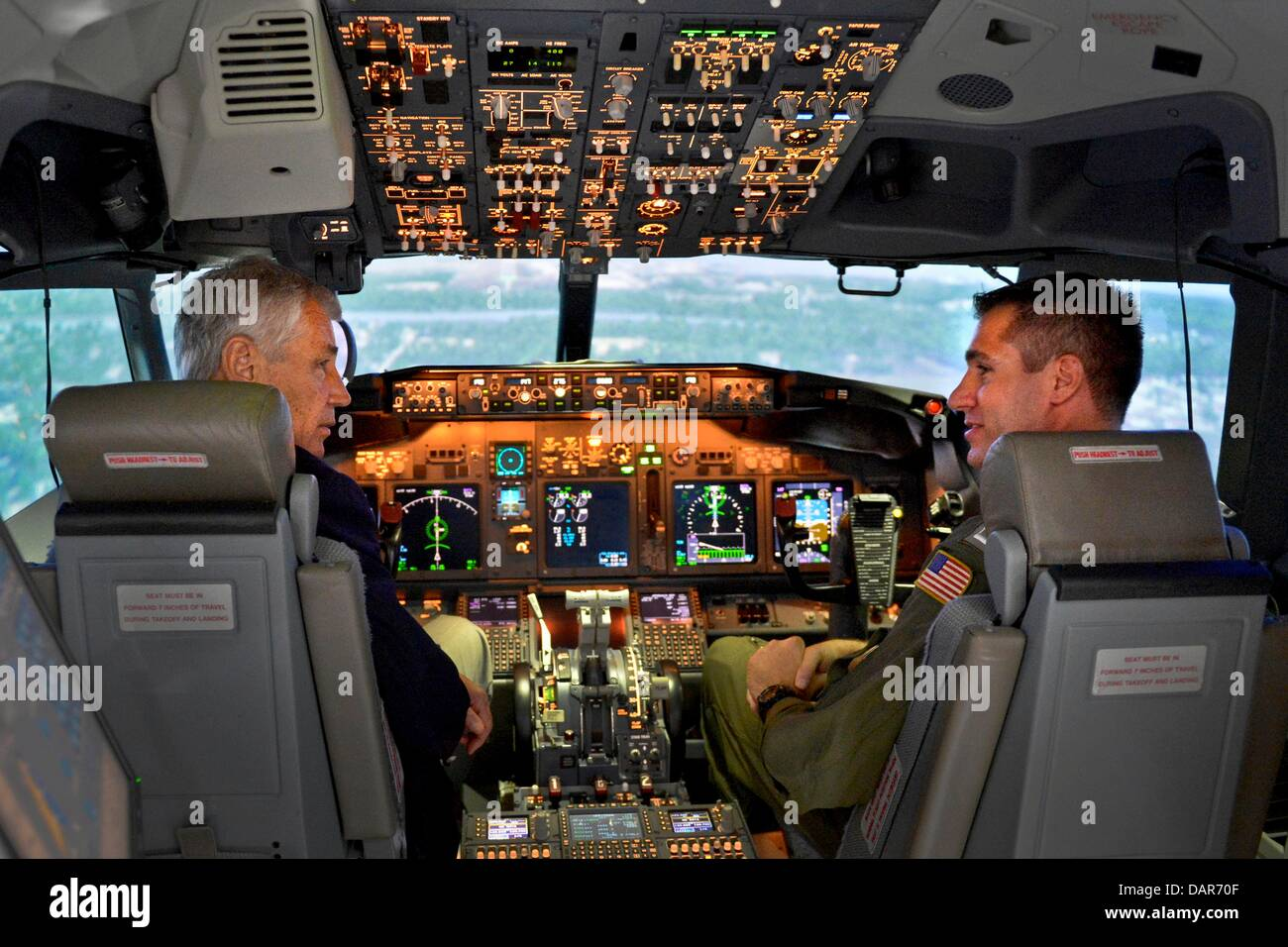 US Secretary of Defense Chuck Hagel, left, sits in the cockpit of a P-8 aircraft flight simulator as he visits the - Stock Image