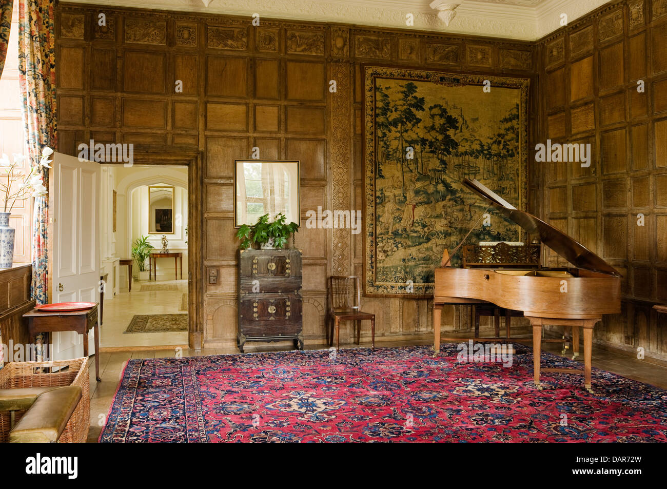Jacobean oak paneled parlour with Flemish tapestry and grand piano in Ampney Park, 17th century English country - Stock Image