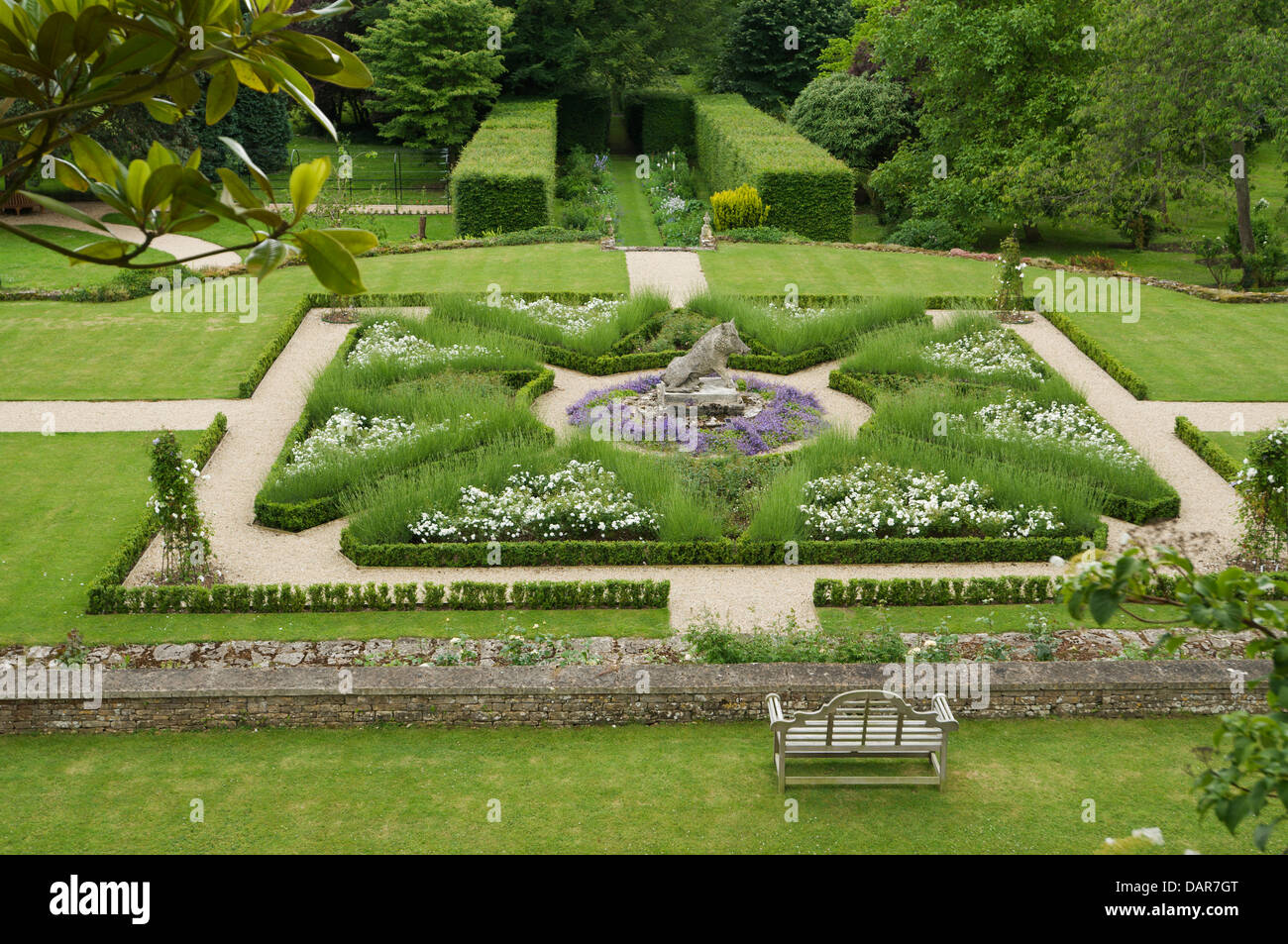 Box hedge borders and paths in garden with stone hog statue in Ampney Park, 17th century English country house - Stock Image