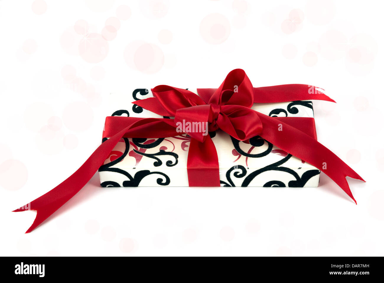Gift wrapped with a red ribbon - Stock Image