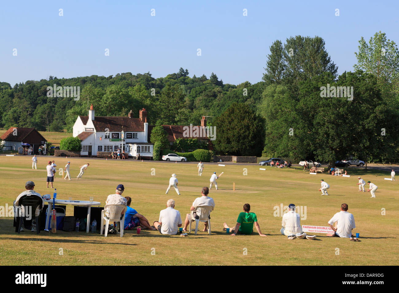 Local team playing a cricket match on village green in front of Barley Mow pub on a summer's evening. Tilford Surrey Stock Photo