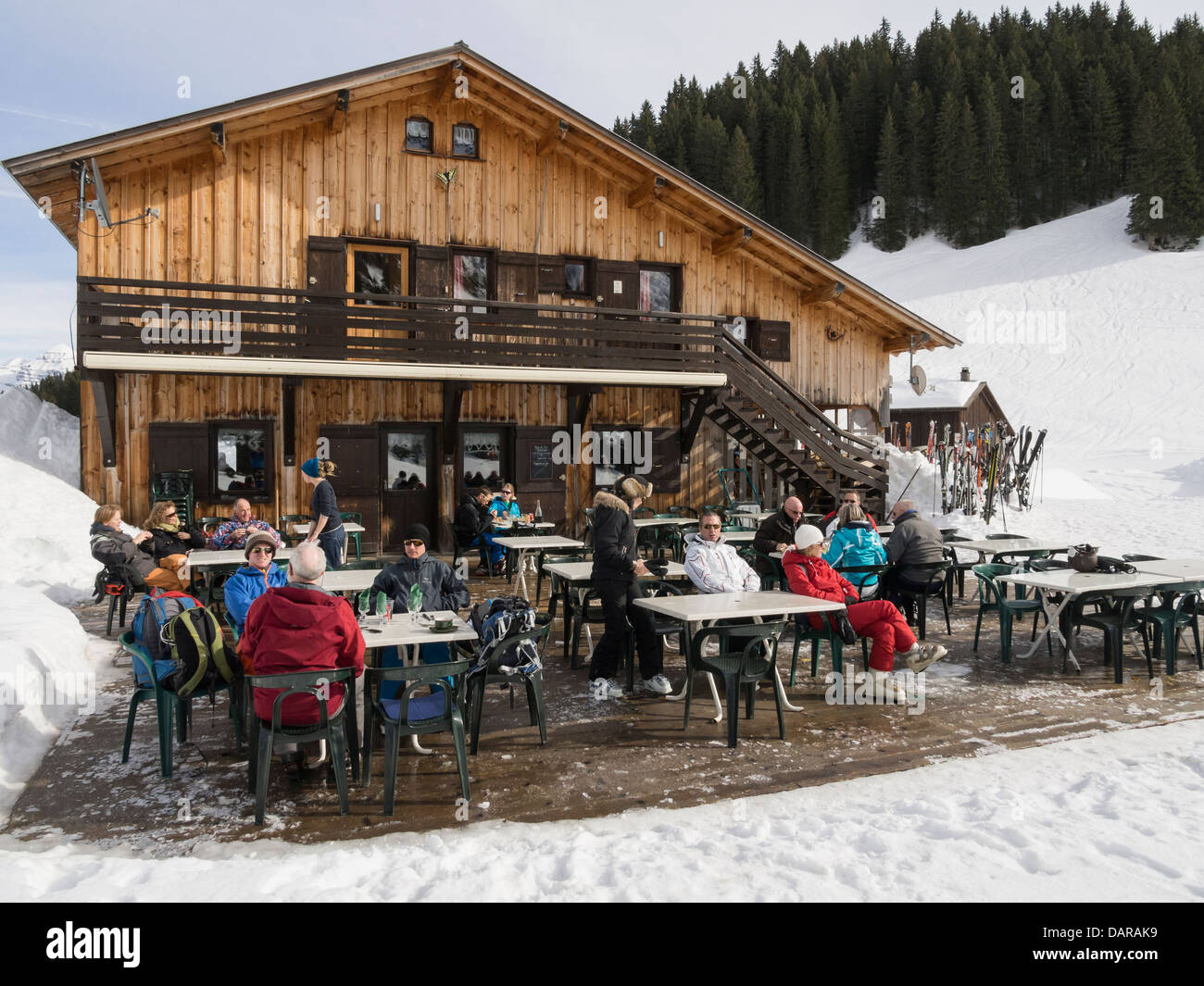 People dining outside Gite du Lac de Gers alpine lakeside ski chalet restaurant in Le Grand Massif in French Alps. - Stock Image