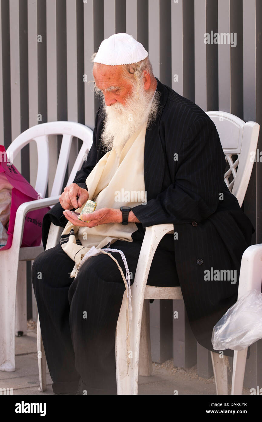Israel Jerusalem City Wailing Western Wall Ha Kotel Plaza orthodox old Jewish man counts money for helping pray - Stock Image