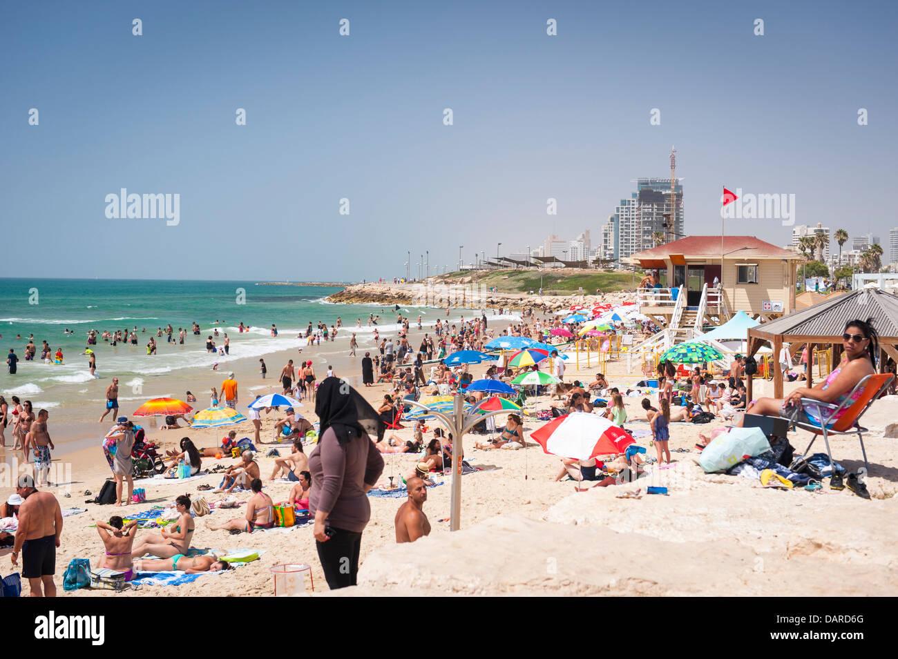 Israel Tel Aviv Jaffa Yafo Manta Ray Beach crowds under parasols umbrellas sonnenschirm sand sea sunbathers sunbathers - Stock Image