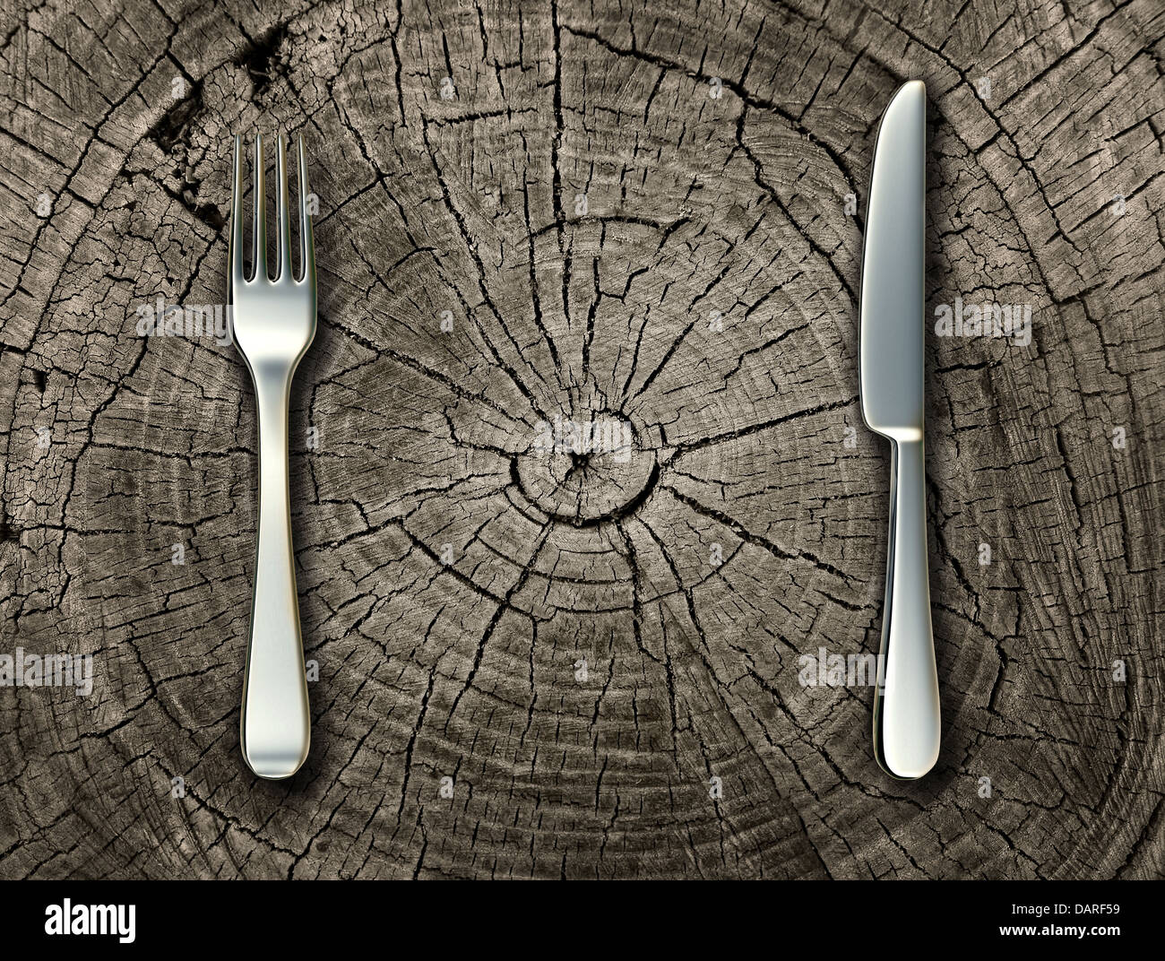 Natural food concept and organic eating healthy lifestyle idea with a silver fork and knife on a cut tree stump - Stock Image