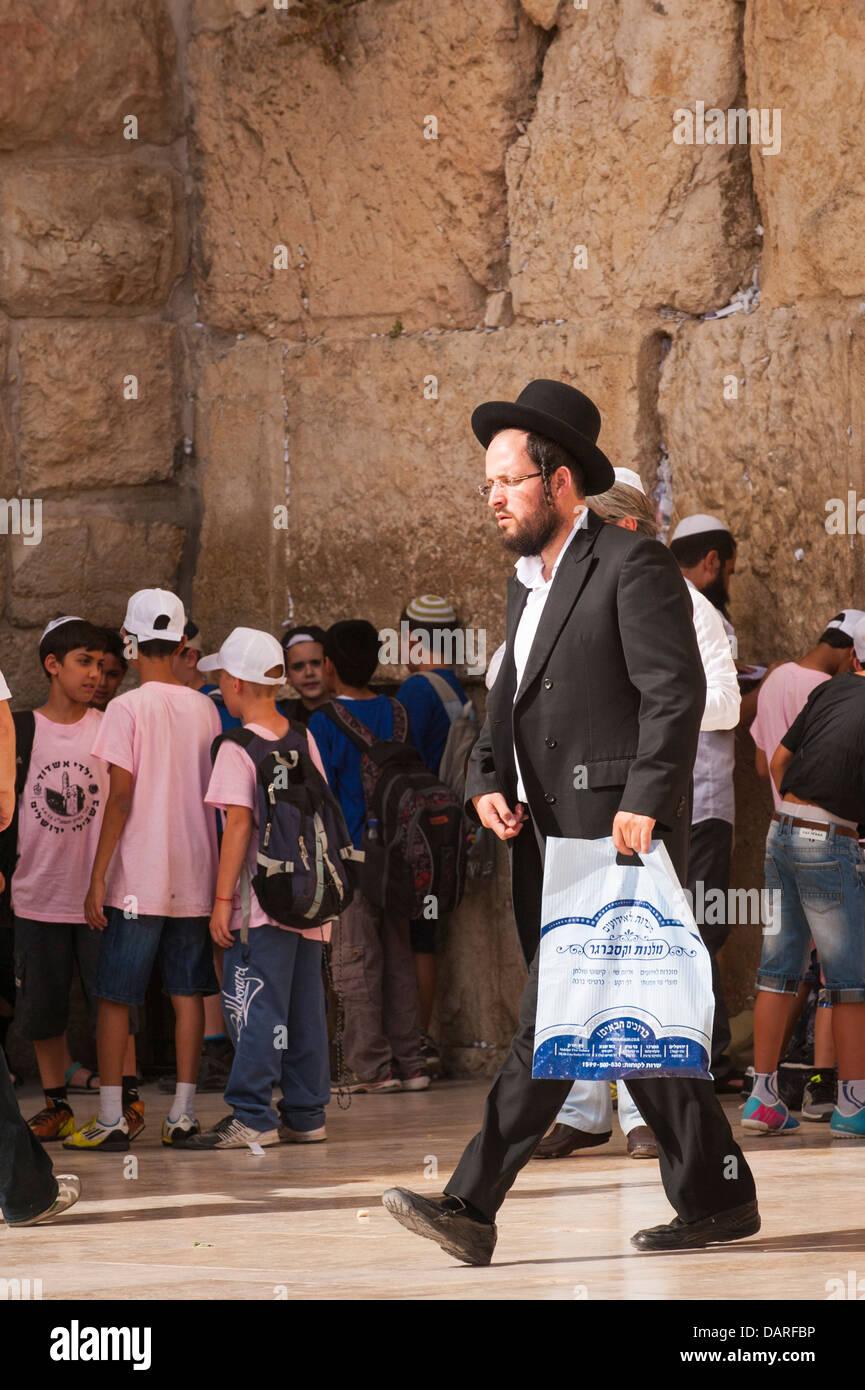 Israel Jerusalem Old City Wailing Western Wall Ha Kotel Plaza Hasidic Chabad orthodox Jew Jewish man walking plastic - Stock Image