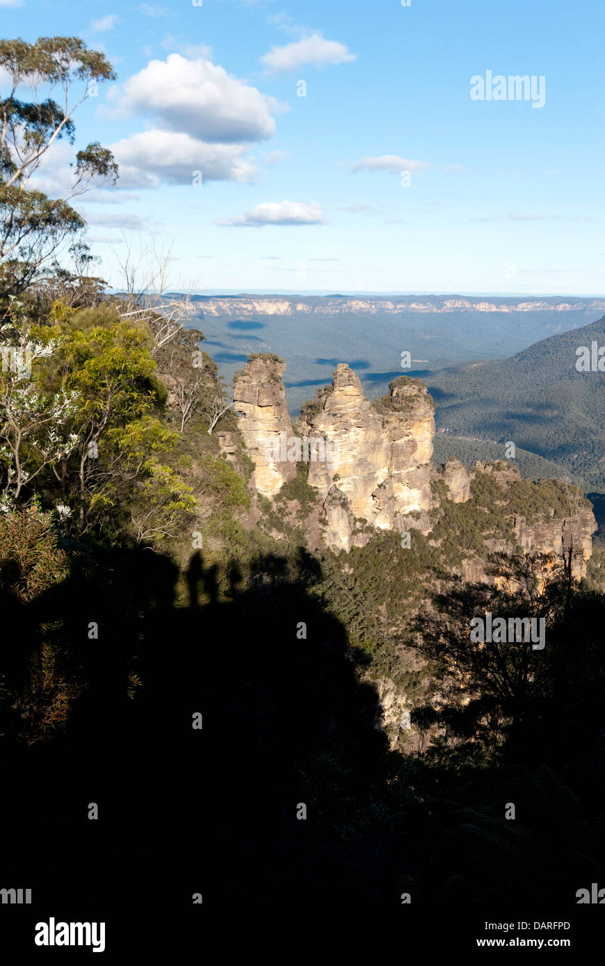 The Three Sisters rock formation at Echo Point, with the shadow of visitors on the viewing platform - Stock Image
