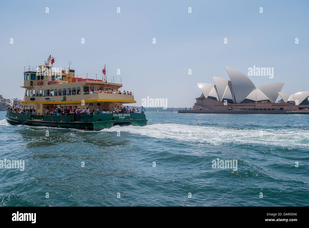 Ferries pass by the majestic Sydney Opera House in busy Sydney Harbour. - Stock Image