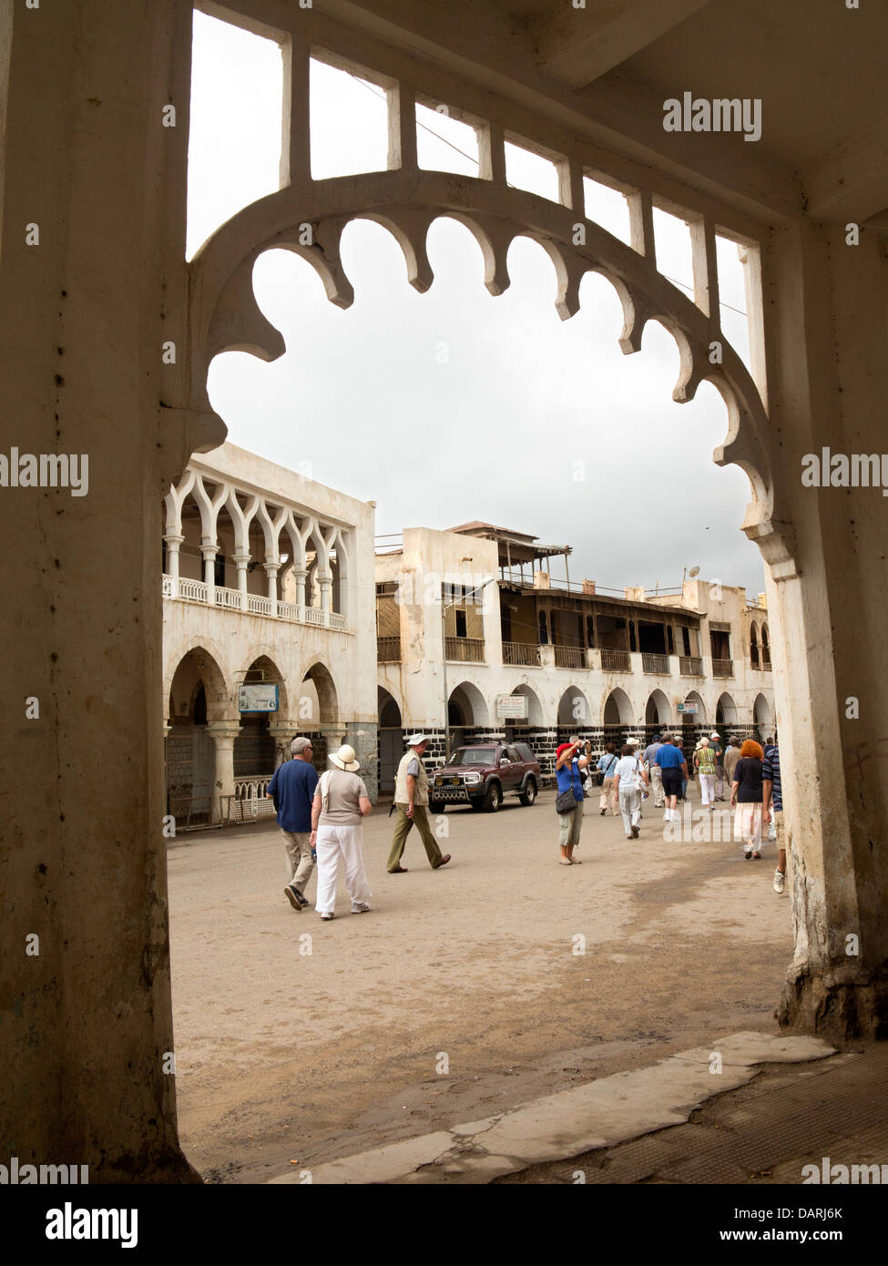 Africa, Eritrea, Massawa, Old Town, group of cruise ship passengers passing Ottoman architecture building - Stock Image